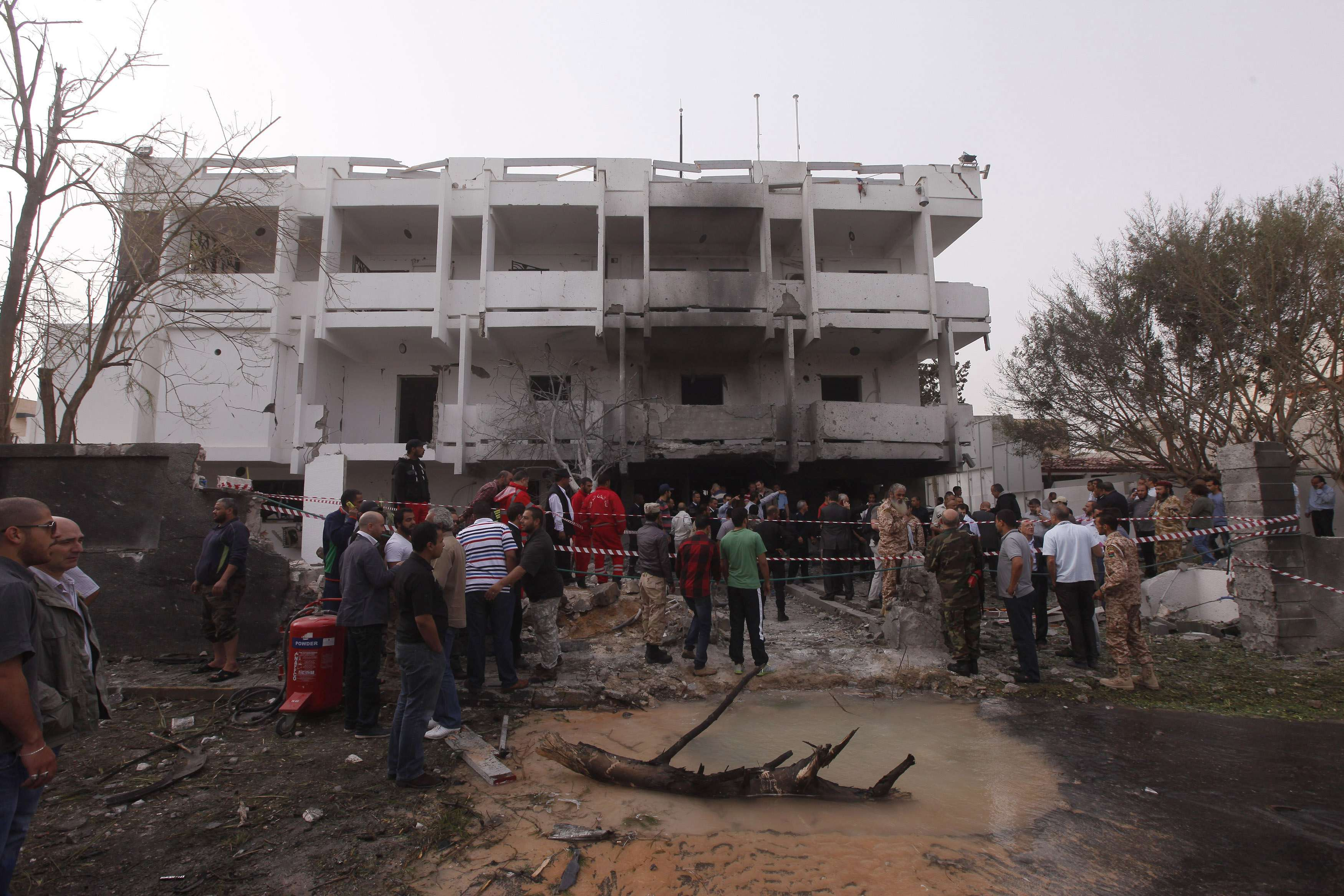 People stand among debris outside the French embassy after the building was attacked, in Tripoli