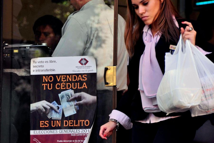 "A woman passes by a sign reading ""Don't sell your ID. It is a crime"" in Asuncion on April 20, 2013, the day before general elections in Paraguay. Signs of a campaign of the Public Prosecutor's office preventing citizens from accepting money for their identity documents, were placed in the streets of Asuncion against electoral fraud in the beginning of April.  AFP PHOTO/Norberto DUARTE"