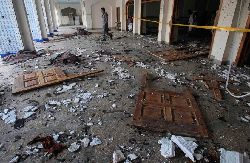 A man walks past broken glass and doors after an explosion in a Shi'ite mosque in Peshawar February 13, 2015. At least 19 people were killed on Friday in the Pakistani city of Peshawar in a gun and bomb attack on the Shi'ite mosque, the latest sectarian violence to hit the South Asian nation. REUTERS/Fayaz Aziz (PAKISTAN - Tags: CIVIL UNREST RELIGION TPX IMAGES OF THE DAY)