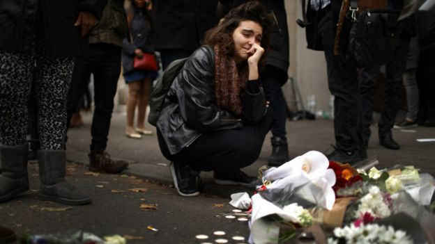 Mulher se solidariza com vítimas em Paris; pelo menos 129 morreram