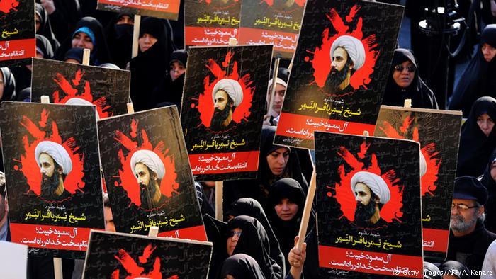 Manifestantes em Teerã carregam cartazes com imagens de Al-Nimr durante protesto contra a Arábia Saudita