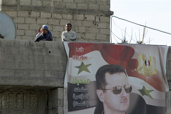 Residentes de um subúrbio de Damasco controlado pelas forças do regime junto a foto de Assad   |  REUTERS/OMAR SANADIKI