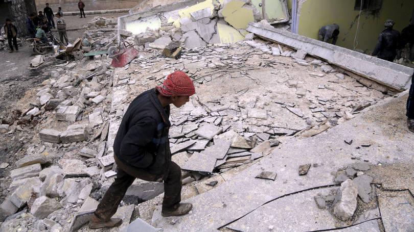 """Menino olha ruínas de sua escola, destruída em bombardeio russo em Aleppo: desde setembro de 2015, a aviação russa bombardeia """"alvos terroristas"""""""