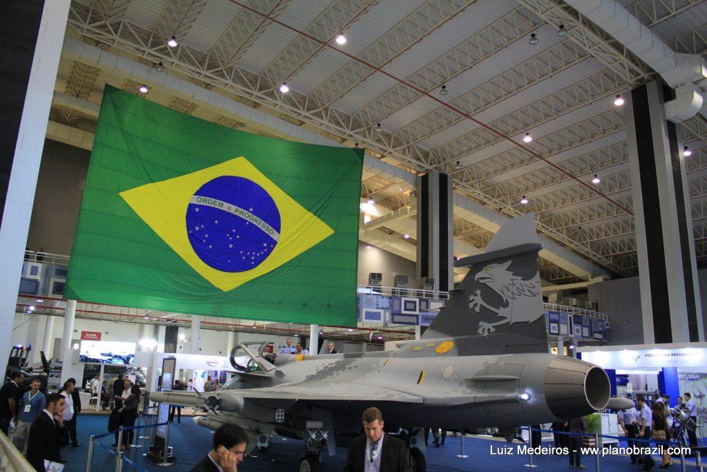 A bandeira do Brasil ao fundo da área interna de exposições e o mock-up do Gripen da FAB