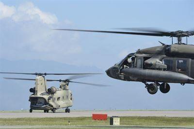 Helicópteros UH-60 BlackHawk e CH-47 Chinook assignados ao 228.º Regimento de Aviação do 1˚ Batalhão da Força-Tarefa Bravo partem da Base Aérea de Soto Cano, em Honduras, para estabelecerem-se nas ilhas Cayman e proporcionar apoio de transporte aéreo durante os esforços de resposta aos danos causados pelo furacão Matthew, a pedido da Agência Internacional para o Desenvolvimento Internacional dos EUA. (Foto: Sgt Siuta B. Ika/Força Aérea dos EUA)