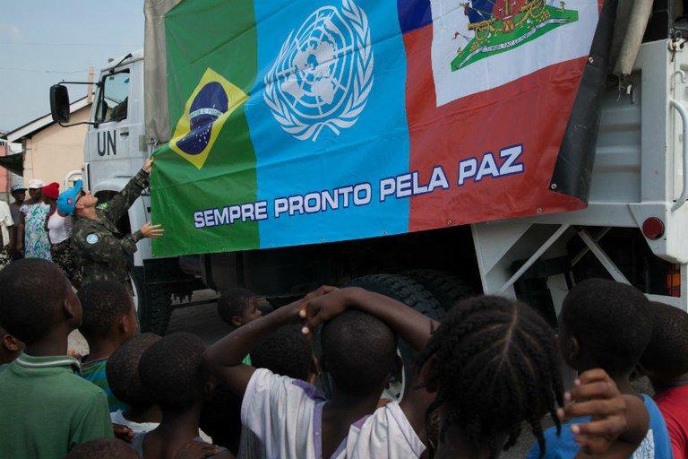 Integrante da Minustah pendura bandeira conjunta do Brasil, da ONU e do Haiti em centro de combate ao cólera, em Porto Príncipe, capital do Haiti, em 25 de abril. Na imagem abaixo (de Logan Abassi), crianças brincam na favela de Cité Soleil, também na capital haitiana, em agosto de 2013
